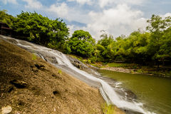 Side view of a waterfall cascading down a cliff Royalty Free Stock Images