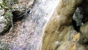 Side view on waterfall on small mountain river flowing in stony riverbed covered with moss. Pure fresh water in spring. Forest. Scenic rocky river in Crimea stock footage