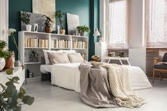 Side view of white bed. Side view of a comfy, white bed with gray and beige blanket next to the window in natural bedroom interior with emerald green wall stock photos