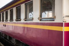 Side view and window of local train in Thailand. Local train looks vintage. Unidentified railway train on the railroad tracks in Bangkok station. Many people in Stock Photography
