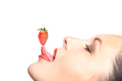 Side view of woman balancing a strawberry Stock Photos