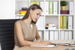 Side view of woman in beige writing with marker Stock Photos