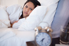 Side view of woman being woken by alarm clock Royalty Free Stock Photography