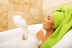 Side view woman blowing a foam, relaxing in bath Royalty Free Stock Images