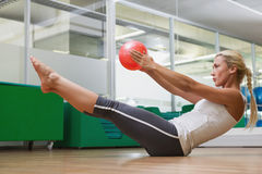Side view of woman in boat pose at fitness studio Stock Photo