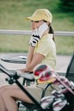 side view of woman in cap polo and golf glove talking on smartphone