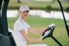 side view of woman in cap and polo riding golf cart