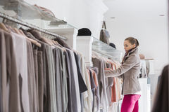Side view of woman choosing sweater in store Stock Images