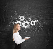 Side view of a woman and cogs and gears on a blackboard Stock Images