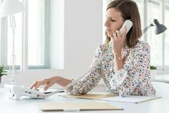 Side view of a woman dialing telephone number Stock Photo