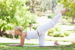 Side view of a woman doing gymnastic exercises on the lawn Stock Image