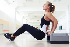 Side view of woman doing press ups on step. Side view of sporty woman doing press ups on step. Muscular female exercising Royalty Free Stock Image