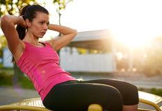 Side view of woman doing situps outside. Royalty Free Stock Photo