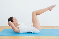 Side view of a woman doing stomach crunches on exercise mat stock photos