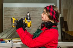 Side view of woman with drill machine in carpentry.  stock photo