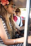Side view of woman driving camper van. Side view of women with friend driving camper van Royalty Free Stock Images