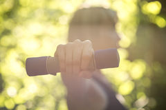 Side view of a woman exercising wth dumbbells in nature Royalty Free Stock Photography