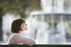 Side View Of Woman In Front Of Blurred Fountain Stock Photo