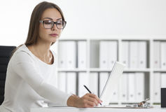 Side view of a woman in glasses writing Royalty Free Stock Image