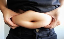 Side view of woman hand catching fat body belly paunch , diabetic risk factorwoman hand catching fat body belly paunch , diabetic. Woman hand catching fat body Stock Images