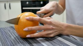 Side view of woman hands cutting fresh grapefruit with knife. Female making fruit salad. Vegetarian concept. HD stock video footage