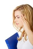 Side view of woman with headache holding a binder Royalty Free Stock Photography