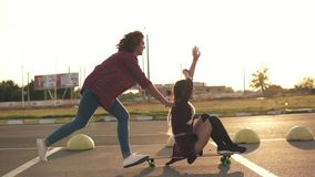Side view of a woman with her hands raised up sitting on a longboard while her friend is pushing her behind and running