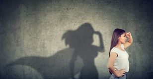Side view of a woman imagining to be a super hero looking aspired stock photography