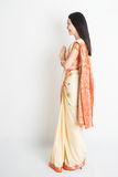 Side view woman in Indian sari dress greeting. Full length side view mixed race Indian Chinese female with sari dress in greeting gesture, standing on plain Royalty Free Stock Photos
