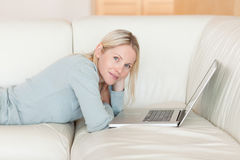 Side view of woman with laptop lying on the couch Stock Photography