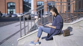 Side view of woman with laptop on stairs in the street stock video footage