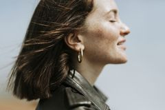 Side view of a woman in leather jacket standing in a park royalty free stock photos