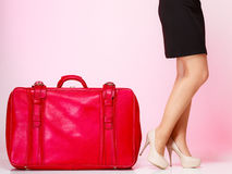 Side view woman legs with red suitcase on pink background Royalty Free Stock Photo