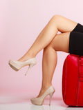 Side view woman legs with red suitcase on pink background Royalty Free Stock Images