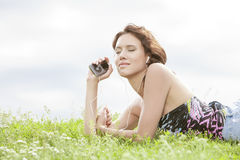 Side view of woman listening to music through MP3 player using headphones while lying on grass against sky Royalty Free Stock Images