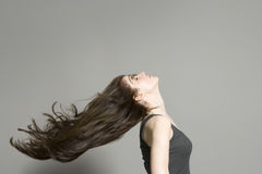 Side View Of Woman With Long Hair Blowing In Wind. Side view of a woman with long brown hair blowing in wind against gray background royalty free stock image