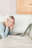Side view of woman lying on the couch surfing the web Stock Photos