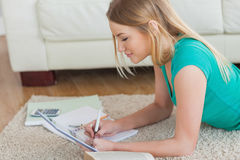 Side view of woman lying on floor working on homework Royalty Free Stock Photography