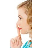 Side view of a woman making silence gesture Stock Image