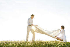 Side view of woman and man spreading picnic blanket on grass during sunny day Stock Image