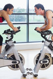 Side view of a woman and man working out at spinning class Royalty Free Stock Images