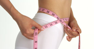 Side view of woman measuring waist Stock Photo