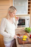 Side view of woman nibbling while cutting vegetables Royalty Free Stock Photos