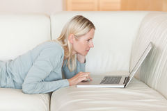 Side view of woman with notebook lying on the sofa Royalty Free Stock Photography