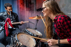 Side view of woman playing drums with man playing guitar. Side view of women playing drums with men playing guitar, rock band concept Royalty Free Stock Image