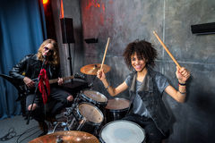 Side view of woman playing drums with man singing into microphone Stock Photography