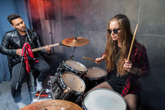 Side view of woman playing drums with man singing into microphone Stock Photos