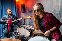 Side view of woman playing drums and man singing into microphone Royalty Free Stock Image