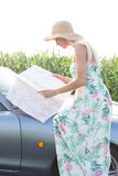 Side view of woman reading map while sitting on convertible Royalty Free Stock Photos