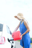 Side view of woman refueling car on country road Royalty Free Stock Photography